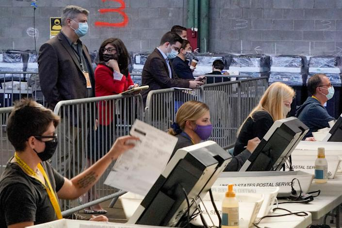 Election observers stand behind a barrier and watch as election office workers process ballots as counting continues from the general election at the Allegheny County elections returns warehouse in Pittsburgh on 6 November. (AP)