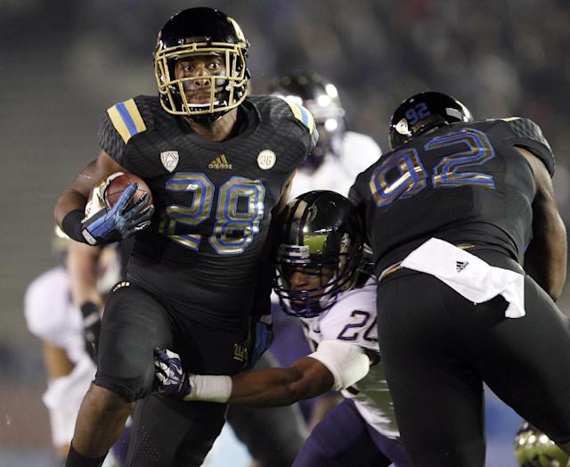 UCLA running back Malcolm Jones (28) tries to get past Washington defensive back Kevin King, who is blocked by UCLA defensive end Brandon Willis, right, during the first half of an NCAA college football game Friday, Nov. 15, 2013, in Pasadena, Calif. (AP Photo/Alex Gallardo)