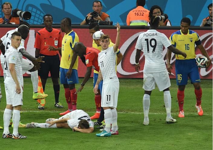 France's Lucas Digne lies on the ground after a tackle which resulted in a red card for Ecuador's Antonio Valencia (R) during their 0-0 Group E match at the Maracana Stadium in Rio de Janeiro during the 2014 FIFA World Cup on June 25, 2014 (AFP Photo/William West)