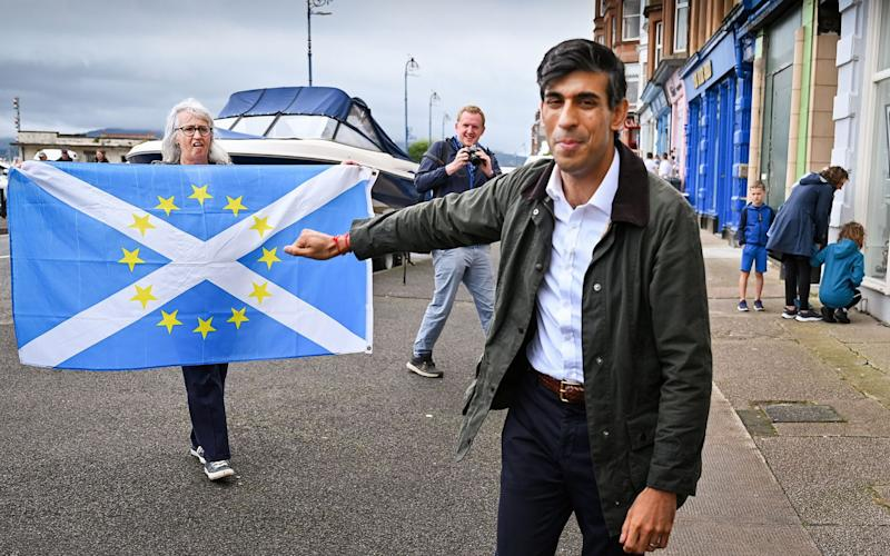 A nationalist demonstrator holds a flag as she welcomes Britain's Chancellor of the Exchequer Rishi Sunak to the Isle of Bute last month - Reuters