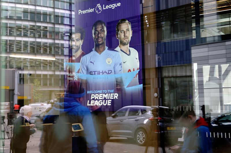 Members of the media are reflected in the glass at the headquarters of the English Premier League in London on March 13, 2020. - The English Premier League suspended all fixtures until April 4 on Friday after Arsenal manager Mikel Arteta and Chelsea winger Callum Hudson-Odoi tested positive for coronavirus. (Photo by Isabel Infantes / AFP) (Photo by ISABEL INFANTES/AFP via Getty Images)