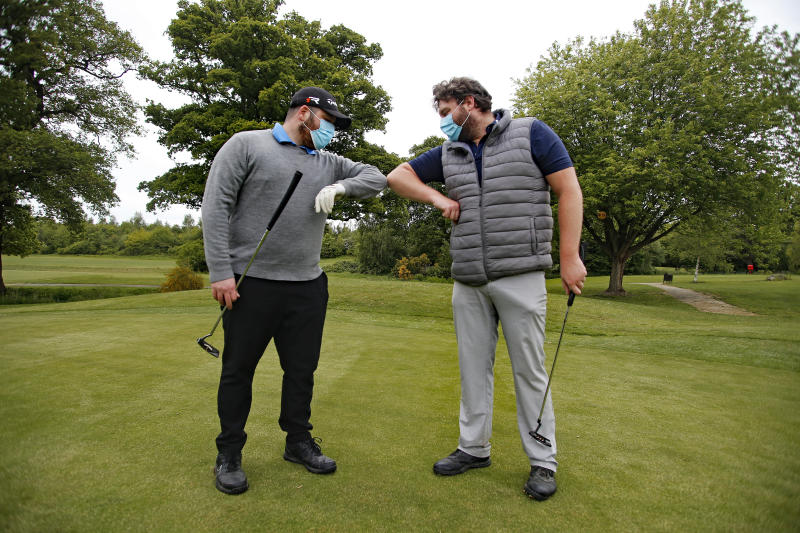Golfers, wearing protective masks, bump elbows at Rookwood Golf Club, Horsham, Sussex, after golfers return to play as restrictions are lifted in England, as the UK continues in lockdown to curb the spread of coronavirus during the pandemic.
