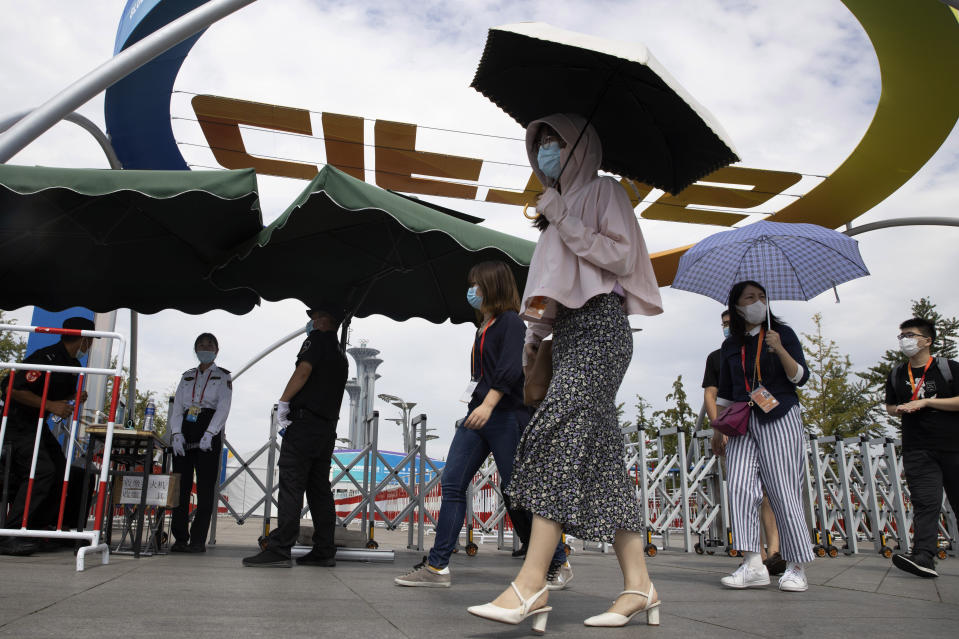 Visitors wearing mask to protect from the coronavirus walks past a venue for the China International Fair for Trade in Services (CIFTIS) to be held in Beijing on Friday, Sept. 4, 2020. As China recovers from the COVID-19 pandemic, business as usual is picking back up with the holding of the China International Fair for Trade in Services. Nearly 2,000 Chinese and foreign enterprises will participate and showcase their newest technology in public health and digital technology (AP Photo/Ng Han Guan)
