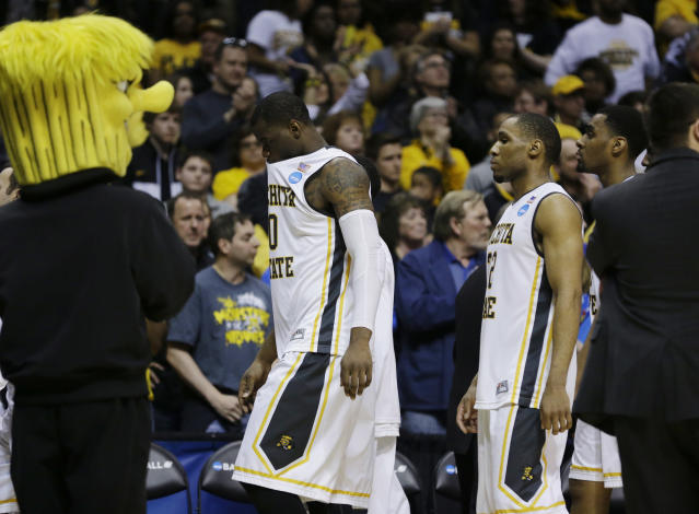 Wichita State forward Chadrack Lufile (0) and guard Tekele Cotton (32) leave the floor after a third-round game against Kentucky the NCAA college basketball tournament Sunday, March 23, 2014, in St. Louis. Kentucky won 78-76. (AP Photo/Jeff Roberson)