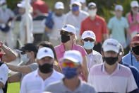 Spectators wear face masks to help curb the spread of COVID-19 while following the lead group along the ninth fairway during the final round of the Workday Championship golf tournament Sunday, Feb. 28, 2021, in Bradenton, Fla. (AP Photo/Phelan M. Ebenhack)
