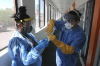 FILE - In this May 7, 2020, file photo, Certified Medical Assistant Shaniya Wood, left, and physician Caleb Lauber, right, test one of over 100 homeless patients who were being isolated in motels for the coronavirus in Gallup, N.M. Some 140 people are participating in the impromptu system, and officials hope it will interrupt a treadmill of infections among Gallup's homeless population. (AP Photo/Morgan Lee, File)
