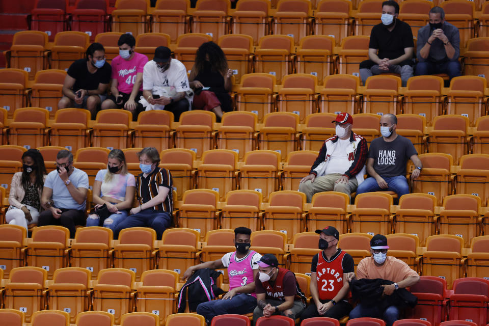 Fans look on during the fourth quarter between the Miami Heat and the Toronto Raptors at American Airlines Arena.