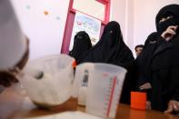 Women wait to receive supplemental nutrition shakes, at malnutrition treatment ward of al-Sabeen hospital in Sanaa
