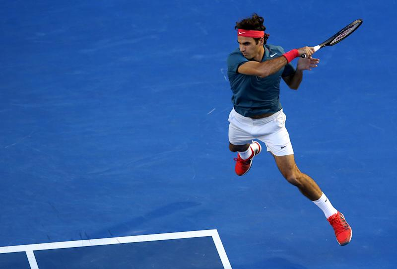Roger Federer of Switzerland leaps for a shot to Andy Murray of Britain during their quarterfinal at the Australian Open tennis championship in Melbourne, Australia, Wednesday, Jan. 22, 2014. (AP Photo/Eugene Hoshiko)