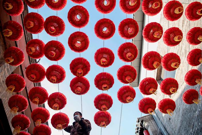 A worker installs traditional Chinese lanterns along an alley ahead of the Lunar New Year of the Ox in Beijing on February 2, 2021.