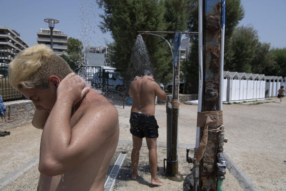Two men take a shower during a heatwave at a beach, in Alimos suburb, southern Athens, Greece, Monday, Aug. 2, 2021. The heat wave is expected to peak Monday, with temperatures inland ranging from 42 to 46 degrees Celsius (107.6 to 114.8 Fahrenheit). Temperatures will remain at 40 Celsius (104 Fahrenheit) or above in much of Greece until at least Friday, meteorologists say. (AP Photo/Michael Varaklas)