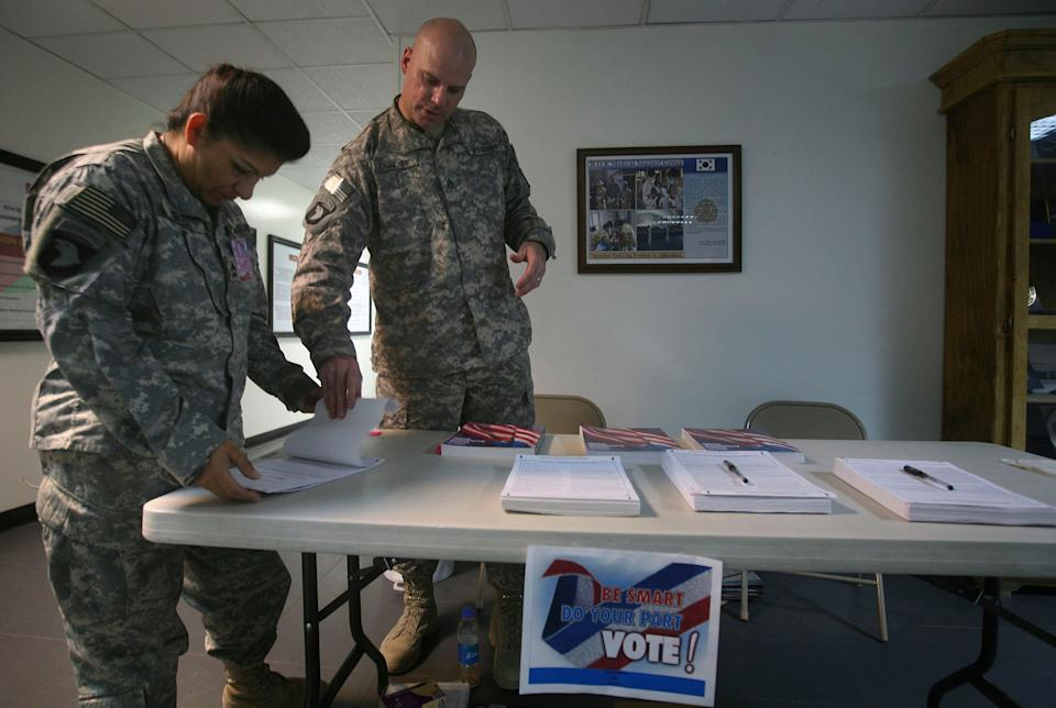 A U.S. service member (left) checks a ballot before filling it out at a U.S. military base in Afghanistan on Oct. 15, 2008. U.S. soldiers, aid workers and military contractors overseas have been allowed extra time for their ballots to arrive at election offices in the U.S. (Photo: Rafiq Maqbool/ASSOCIATED PRESS)