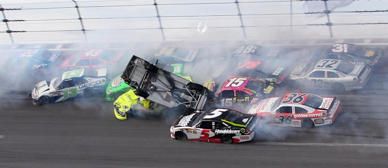 Tony Stewart (14) flips over as Kasey Kahne (5), Clint Bowyer (15), Dave Blaney (36), Terry Labonte (32), Regan Smith (78), Jeff Burton (31), Jimmie Johnson (48), crash around him during the NASCAR Sprint Cup auto race at Talladega Superspeedway in Talladega, Ala., Sunday, Oct. 7, 2012. Also involved in the wreck were Paul Menard (27), Casey Mears (13), Aric Almirola (43), Dale Earnhardt Jr. (88), David Ragan (34) and Sam Hornish Jr. (22). (AP Photo/Dale Davis)