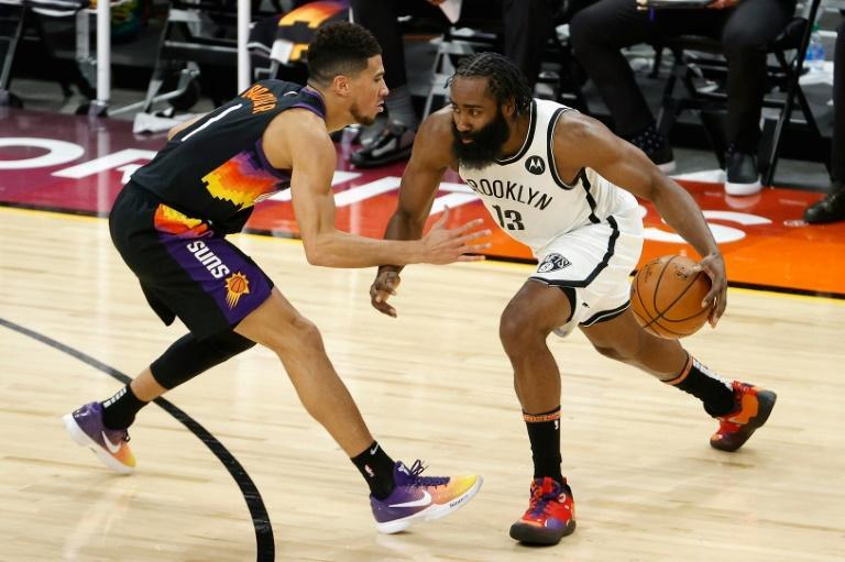Brooklyn Nets star James Harden, right, drives the ball against Devin Booker of the Phoenix Suns during the second half of the NBA game at Phoenix Suns Arena
