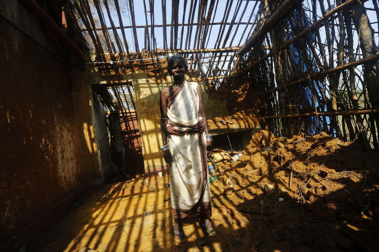 A woman stands inside her damaged house after Cyclone Phailin hit Gopalpur village, in Ganjam district in the eastern Indian state of Odisha October 14, 2013. A mass evacuation saved thousands of people from India's fiercest cyclone in 14 years, but aid workers warned a million would need help after their homes and livelihoods were destroyed. Cyclone Phailin was expected to dissipate within 36 hours, losing momentum on Sunday as it headed inland after making landfall from the Bay of Bengal, bringing winds of more than 200 kph (125 mph) that ripped apart tens of thousands of thatched huts, mangled power lines and tore down trees. REUTERS/Adnan Abidi (INDIA - Tags: DISASTER ENVIRONMENT TPX IMAGES OF THE DAY)