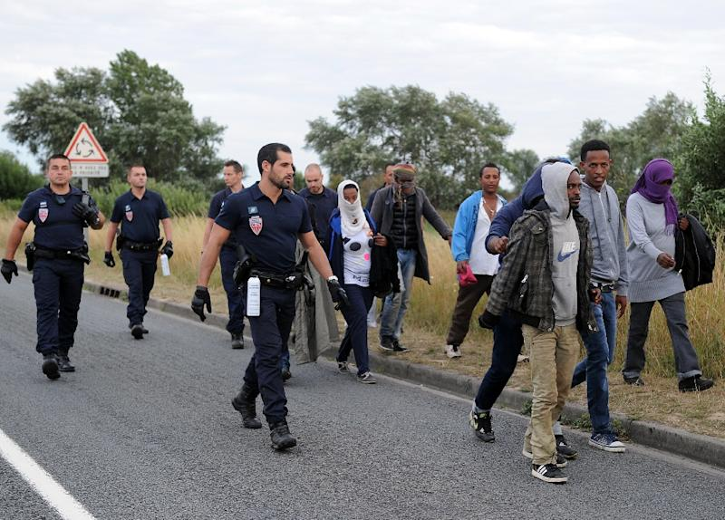 Policemen escort a group of migrants walking in Coquelles near the northern French port of Calais on August 3, 2015 (AFP Photo/Francois Lo Presti)