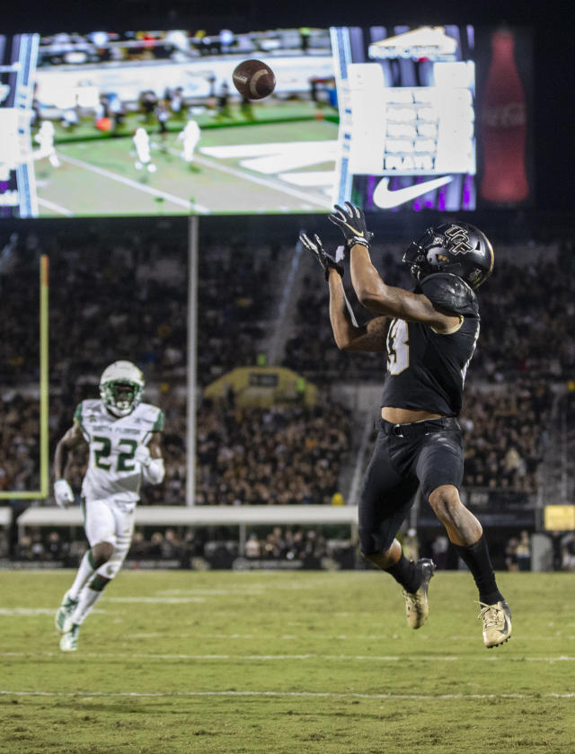 Central Florida wide receiver Eddie McDoom (13) catches a touchdown pass in front of South Florida defensive back Mekhi LaPointe (22) during the first half of an NCAA college football game Friday, Nov. 29, 2019, in Orlando, Fla. (AP Photo/Willie J. Allen Jr.)