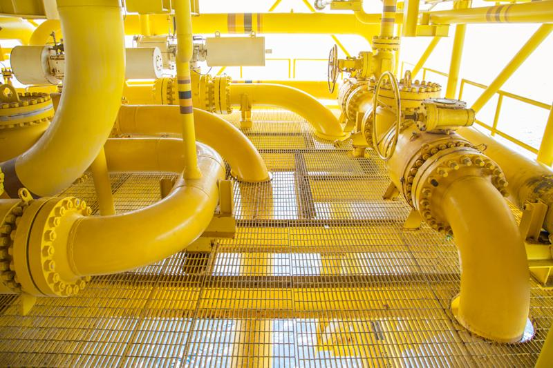 Yellow piping snaking through an industrial site.
