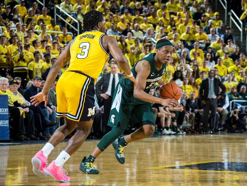 Michigan guard Zavier Simpson (3) defends Michigan State guard Cassius Winston, right, in the first half of an NCAA college basketball game at Crisler Center in Ann Arbor, Mich., Sunday, Feb. 24, 2019. Michigan State won 77-70. (AP Photo/Tony Ding)