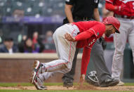 Cincinnati Reds' Nick Senzel reacts after scoring on a wild pitch thrown by Colorado Rockies relief pitcher Jordan Sheffield in the ninth inning of a baseball game Sunday, May 16, 2021, in Denver. (AP Photo/David Zalubowski)