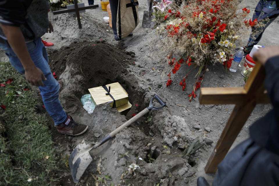 Boxes containing the flowers, lime and other symbolic elements used in the cross-raising ceremony are buried atop the grave of Luz Maria Gonzalez, as her family marks nine days since her burial, in the Municipal Cemetery of Valle de Chalco on the outskirts of Mexico City, Saturday, July 4, 2020. Maria Luz Gonzalez, 56, who had long suffered from asthma, diabetes and hypertension, died two days after her son, who was hospitalized for breathing problems and a cough before dying of complications said to be related to pneumonia and undiagnosed diabetes. (AP Photo/Rebecca Blackwell)