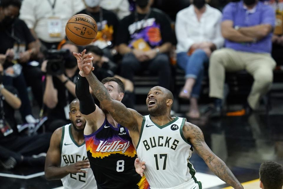 Milwaukee Bucks forward P.J. Tucker (17) battles with Phoenix Suns forward Frank Kaminsky (8) for a loose ball as Bucks forward Khris Middleton (22) looks on during the first half of Game 1 of basketball's NBA Finals, Tuesday, July 6, 2021, in Phoenix. The Suns defeated the Bucks 118-105. (AP Photo/Ross D. Franklin)