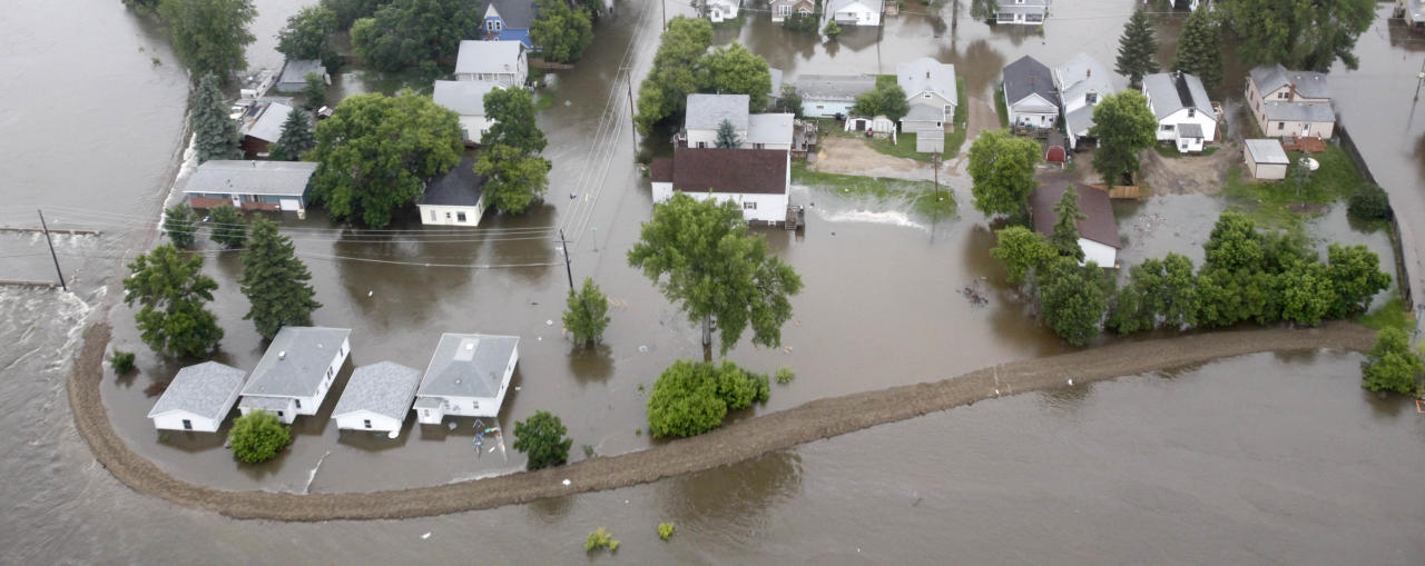 In this aerial photo the flood waters of the Souris River breech a levee, left, and flood a neighborhood Friday, June 24, 2011 in Minot, N.D. The Souris River set a record for flooding, rising so quickly that it could be seen climbing up the side of homes in the North Dakota city. (AP Photo/Charles Rex Arbogast)