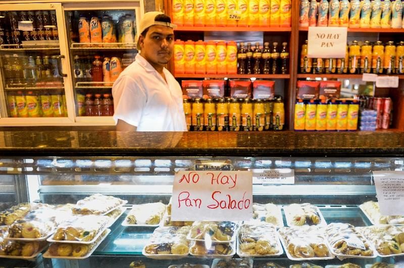 """A sign reading """"No Bread"""" is displayed at a bakery in Caracas on February 25, 2016 as record shortages of basic goods, runaway inflation and an escalating economic crisis cripple businesses"""