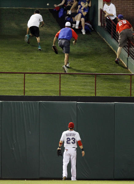 Texas Rangers center fielder Craig Gentry watches fans chase down Detroit Tigers Miguel Cabrera's solo home run in the fifth inning of a baseball game against the Texas Rangers Sunday, May 19, 2013, in Arlington. (AP Photo/John F. Rhodes)