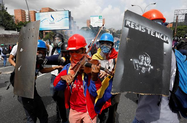<p>A demonstrator plays the violin as others protect him while clashing with riot security forces during a rally against President Nicolas Maduro in Caracas, Venezuela May 24, 2017. (Photo: Carlos Garcia/Reuters) </p>