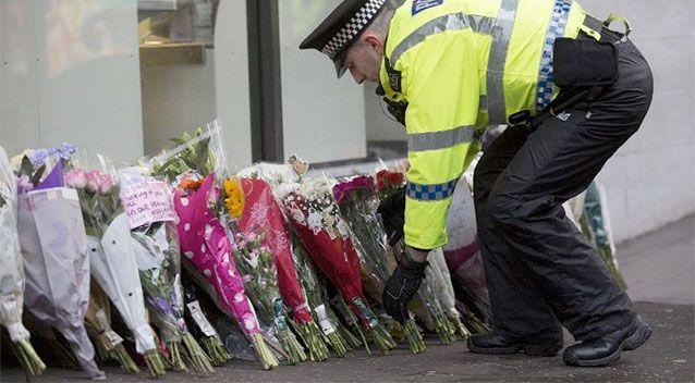 A police officer arranges floral tributes left by members of the public for victims of Monday's refuse truck accident in Glasgow. Photo: AFP