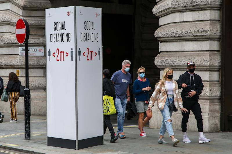"LONDON, UNITED KINGDOM - 2020/08/31: Members of public wearing face masks walk past a ""Social Distancing"" sign at Regents Street during coronavirus pandemic. It is mandatory to wear face masks while travelling. (Photo by Dinendra Haria/SOPA Images/LightRocket via Getty Images)"