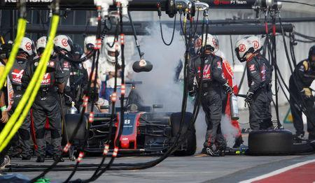 Formula One - F1 - Australian Grand Prix - Melbourne, Australia - 26/03/2017 - Smoke billows from the car of Haas driver Romain Grosjean of France in the pits during the Australian Formula One Grand Prix. REUTERS/Brandon Malone
