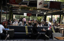 People sit in a re-opened cafe in Ankara, Turkey, Tuesday, June 1, 2021. Cafes and restaurants have re-opened in Turkey after President Recep Tayyip Erdogan's announcement Monday. Most of these establishments have stayed closed down for over a month and a half and Tuesday is their first day back at work.(AP Photo/Burhan Ozbilici)