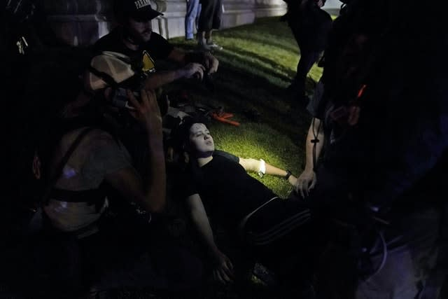 A protester lays injured during clashes with police