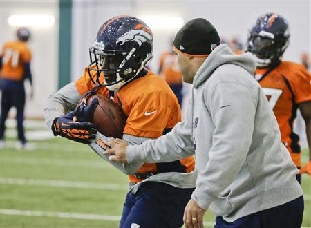 Denver Broncos running back Knowshon Moreno (L) runs a drill as an assistant tries to strip the ball from him during their practice session for the Super Bowl at the New York Jets Training Center in Florham Park, New Jersey January 30, 2014. REUTERS/Ray Stubblebine