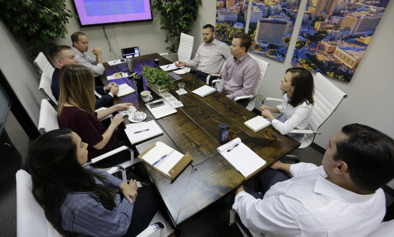 Bethany Babcock, co-owner of Foresite Commercial Real Estate, second from right, takes part in a staff meeting at her office in San Antonio, Tuesday, July 23, 2019.  For many small business owners, being a boss means helping staffers when they struggle Babcock, who runs a family friendly business, has bought a plane ticket for a staffer who needed to visit a relative on life support and paid moving expenses for a staffer who was having family problems, as well as permitting staff to bring their children to work.(AP Photo/Eric Gay)