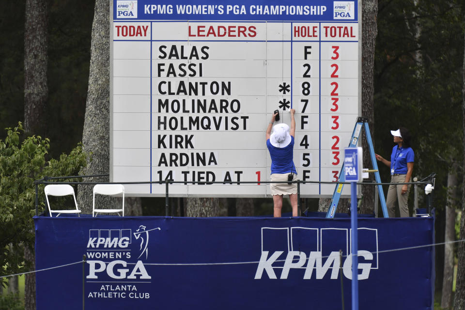 Event staff change scores on a leaderboard during the first round of the Women's PGA Championship golf tournament at Atlanta Athletic Club in Johns Creek, Ga., Thursday, June 24, 2021. (Hyosub Shin/Atlanta Journal-Constitution via AP)