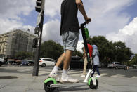 A man rides an electric scooter in Paris, Monday, Aug. 12, 2019. The French government is meeting with people who've been injured by electric scooters as it readies restrictions on vehicles that are transforming the Paris cityscape. The Transport Ministry says Monday's closed-door meeting is part of consultations aimed at limiting scooter speeds and where users can ride and park them. (AP Photo/Lewis Joly)