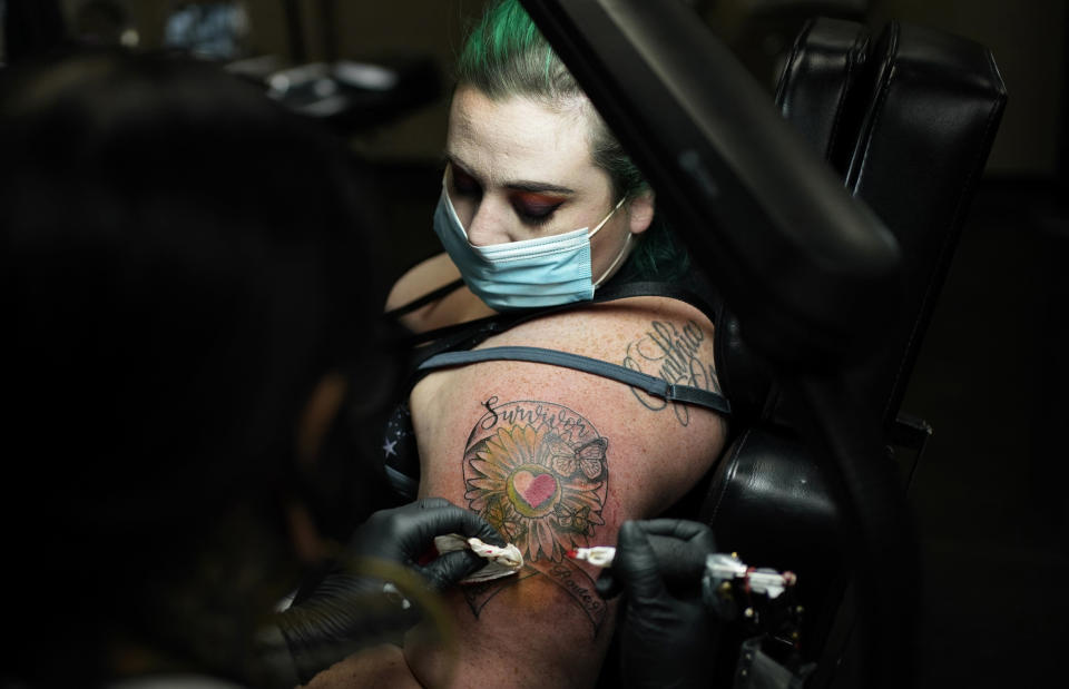 Tattoo artist Jaded Moon gives a tattoo to Shannon Loveless at an event put on by Healing Ink to give tattoos to survivors of the 2017 mass shooting at a country music festival in Las Vegas, Wednesday, Sept. 30, 2020, in Las Vegas. The event was held for survivors the day before the third anniversary of the deadliest shooting in recent U.S. history. (AP Photo/John Locher)