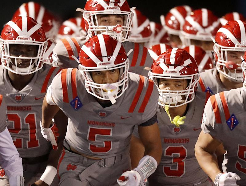 Santa Ana Mater Dei wide receiver Bru McCoy leads his teammates onto the field.