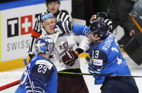Finland's Mikael Ruohomaa, right, scuffles with Latvia's Andris Dzerins during the Ice Hockey World Championship group B match between Finland and Latvia at the Arena in Riga, Latvia, Sunday, May 30, 2021. (AP Photo/Sergei Grits)