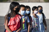 Masked students wait to be taken to their classrooms at Enrique S. Camarena Elementary School, Wednesday, July 21, 2021, in Chula Vista, Calif. The school is among the first in the state to start the 2021-22 school year with full-day, in-person learning. (AP Photo/Denis Poroy)