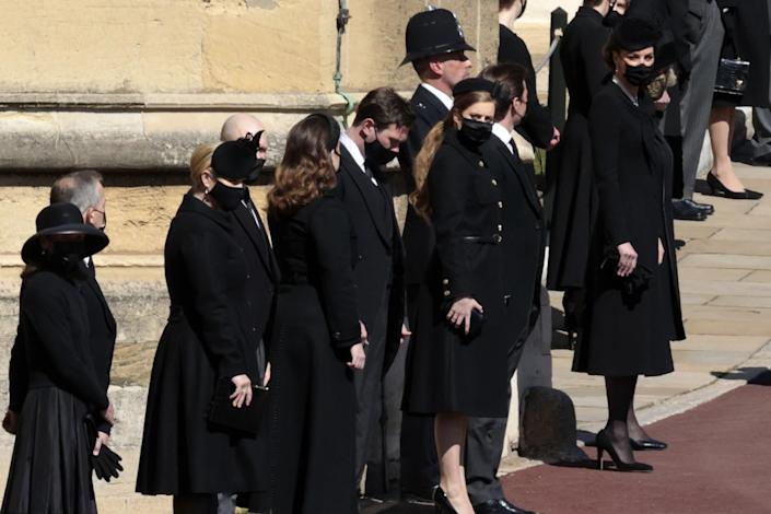 Kate, Duchess of Cambridge, and other masked family members stand along a road on the grounds of Windsor Castle.