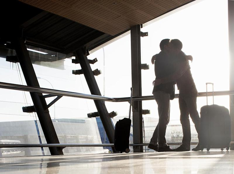 Two men embrace at an airport.