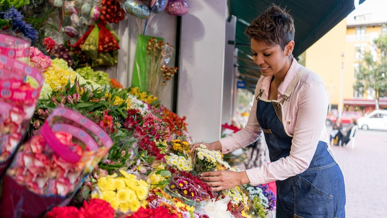 Portrait of a happy female florist organizing flowers at the stand - small business concepts.