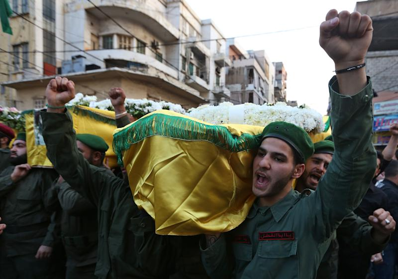 Hezbollah members chant slogans as they carry the coffins of four people, including Radwan Fares, a Lebanese national who headed the facility's security, who were killed a day after two suicide bombings struck the Iranian Embassy in Beirut, during their funeral procession, in the southern suburb of Beirut, Lebanon, Wednesday, Nov. 20, 2013. Thousands of people attended the funerals in Ghobeiri, a stronghold of Hezbollah in southern Beirut. At least 23 people were killed and more than 140 were wounded in Tuesday's twin suicide attacks. (AP Photo/Bilal Hussein)