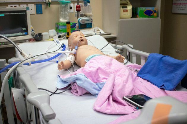 A baby mannequin used for training lies in a pediatric ICU bed at SickKids in Toronto. The baby can breathe and blink and is highly realistic.