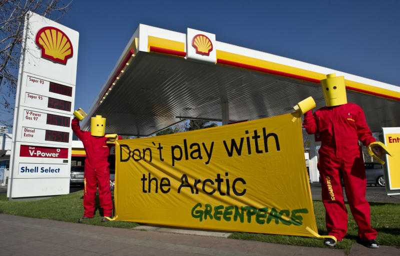 Greenpeace activists hang a banner on July 24, 2014 in front of a Shell gas station in Santiago, Chile