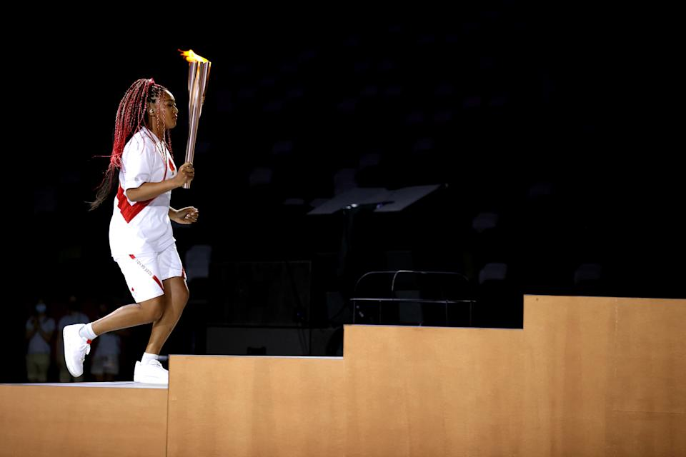 TOKYO, JAPAN - JULY 23: Naomi Osaka of Team Japan carries the Olympic torch towards the Olympic cauldron during the Opening Ceremony of the Tokyo 2020 Olympic Games at Olympic Stadium on July 23, 2021 in Tokyo, Japan. (Photo by Hannah McKay - Pool/Getty Images)